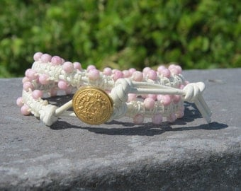 3mm pink Czech glass beads, white leather, white cord wrapping, wrap bracelet and a gold toned crest button - fit for royalty!
