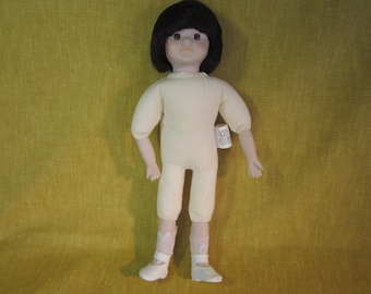 "13"" cloth doll with dark brown hair,glass eyes,socks and shoes"