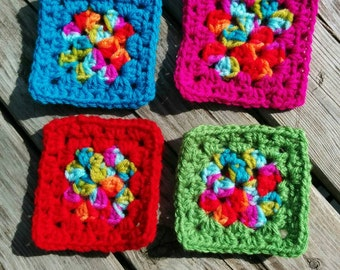 Kit of four square crocheted coasters red, blue, green and pink
