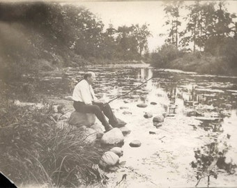 Vintage Snapshot 1920 Man Alone Sits on Rock Fishing w Pole Into River