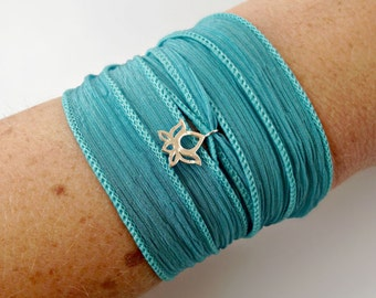 teal silk wrap with sterling silver lotus flower charm.