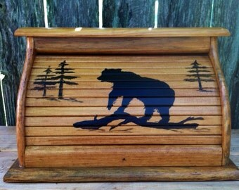 Bread box with black bear standing on alpine log with pine trees in the distance hand painted in black silloutte on stained wood finish