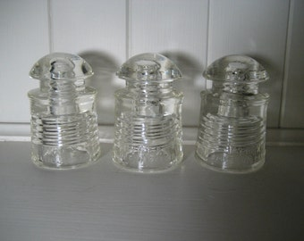 collection of three clear Pyrex glass telephone insulators