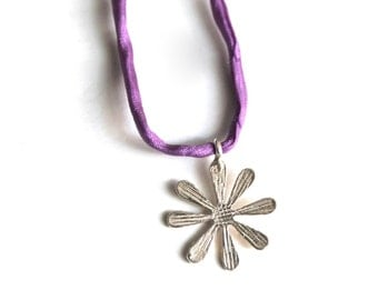 silver flower necklace on green or purple cord-