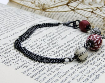 Delicate black coloured chain bracelet red fabric,, book page and faceted glass beads
