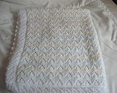 hand knitted baby blanket in white with lemon, mint green