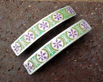 Small etched silver barrettes. Pair of hand etched metal hair barrettes with purple flower wheel design on a green background.