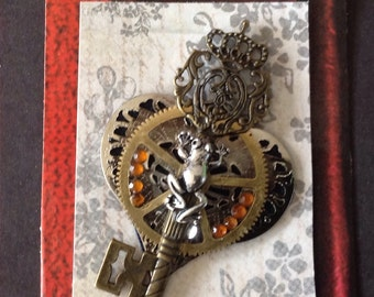 Steampunk;victorian;necklace;brooch;filigree;mixed media;collage;repurposed;recycled;gears;key;wings