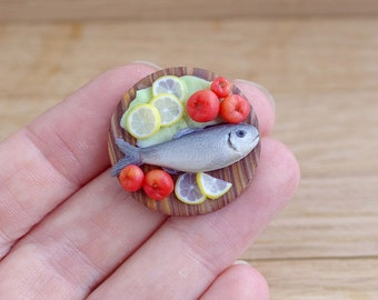 Fish with vegetables . Miniature food for a dollhouse . On a scale of 1:12