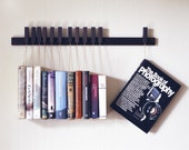Custom made wooden book rack / bookshelf in fumed Oak. Pins also work as bookmarks. Bookcase
