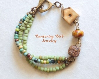 Ceramic Bird House Bracelet, Multi Strand Bracelet with Green Seed Beads, Pottery and Lampwork Glass Beads, Brass Bracelet, Artisan Jewelry