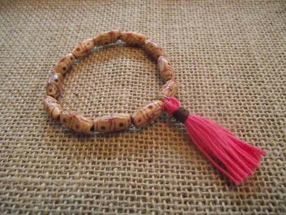 Patterned wood bead bracelet with pink tassel