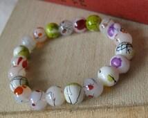 Bracelet. Spring meadow inspired white, green, purple, glass beaded bracelet.