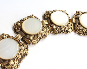 Chunky vintage gold tone cuff bracelet with leaf design, faux pearls, thermoset cabs