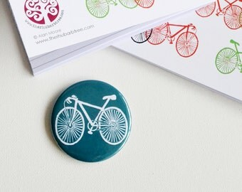 On Your Bike Fridge Magnet 58mm fridge magnets with a white bike on a teal background