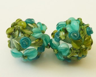 Glass lampwork bead set in light turquoise with raised flower decoration.