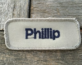 "Phillip. An off white shirt patch that says ""Phillip"" in blue print"