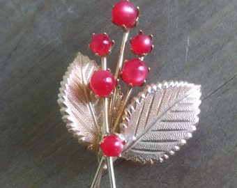 Gold pin with red acccents