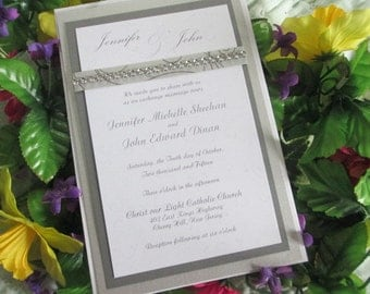Silver swirls elegant back pocket wedding invitation with bling embossed and layered with response card and envelopes
