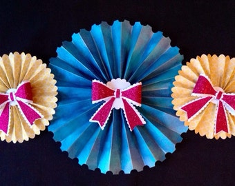 Set of 3 blue/yellow paper rosettes with pink bows decorations.