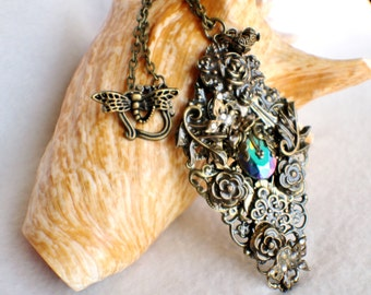 Rose pendant with layers of bronze floral filigree, leafs and butterfly's surrounding a glass jewel.