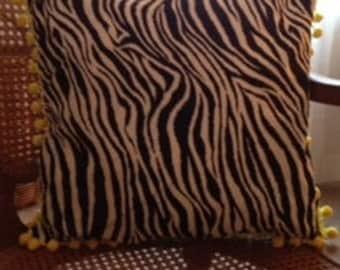 Decorative zebra print pillow with yellow pom-poms