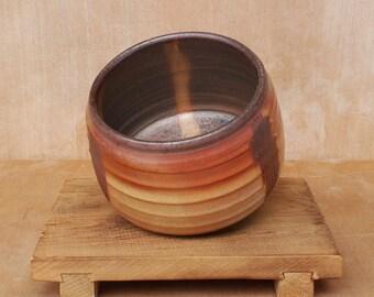 Textured flat base stoneware tea bowl with shino glaze