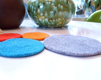 felted wool trivet, small, in grey, teal, and bright oranges (1972)