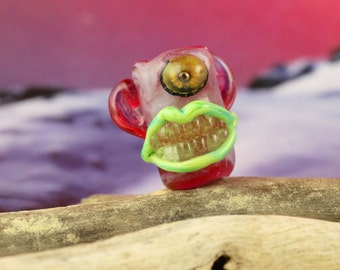 Eek pretty in pink, grinning one eyed monster dread bead