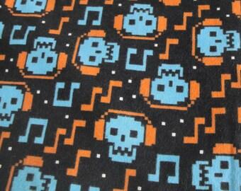Skull flannel fabric black with blue skulls wearing orange headphones, musical notes, 1 yard flannel