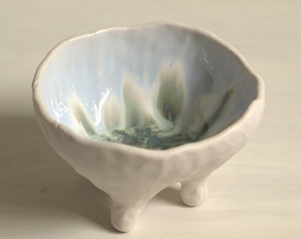 Organic porcelain bowl with feet in white, pale blue and green.