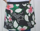 Women's or men's half apron black with pink and white flowers.  Two pockets, heavy cotton fabric.