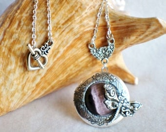 Dragonfly photo locket, round silver tone locket with purple cats eye cabochon and silver dragonfly on front cover.