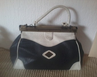 blue leather bag with navy and white on the side clasps