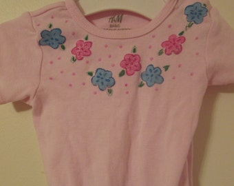 For your little flower, a hand-painted onesie with the colors of your choice.