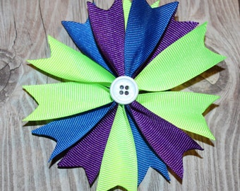 Spike hair bow with green, purple, and blue ribbon and a button center on an alligator clip with a headband