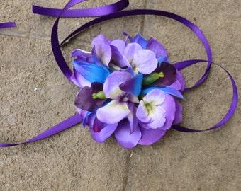 Purple and blue wrist corsage made with purple hydrangeas, galaxy orchids, purple ribbon ties, royal blue, royal purple