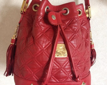 Vintage MCM genuine leather red mini hobo bucket shoulder bag with golden logo charms and fringes. Square stitch.Designed by Michael Cromer.