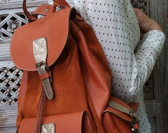 Handmade orange leather bagpack with gold snake leather details . Custom colors also available