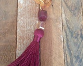 Long tortoise lucite-loop necklace with garnet tassel.