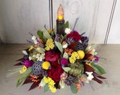 Dried flower and fruit harvest centerpiece. With battery flickering primitive candle. Nice for your holiday table.