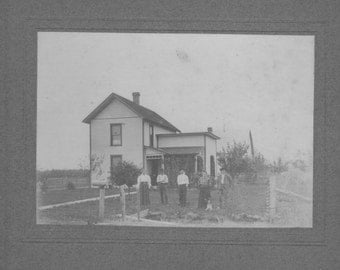 Early 1900s cardboard of family standing in front of the old homeplace.