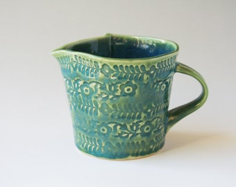Small green ceramic jug with impressed floral motif