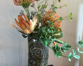 Green ceramic vase with faux proteas, curly willow and assorted greens.