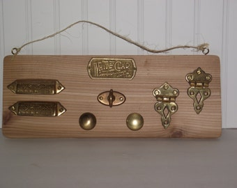"""A vintage grouping of solid brass antique """"ice box"""" hardware, mounted onto a section of cedar."""
