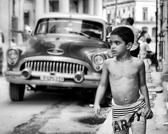 El chico, Havana, Cuba. Art photography in black and white with a young boy and an old car, Ford..