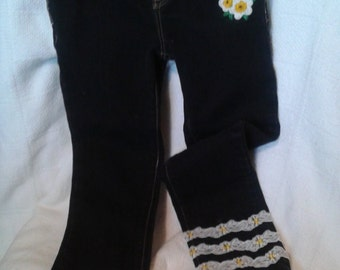 Girls embellished jeans.  Black jeans with flower appliques front and back, bottom of legs have 3 rows of fancy lace with flowers applied.