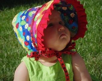 Baby bonnet with ladybug print and oversized brim