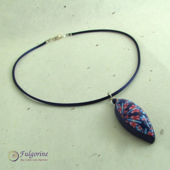 Pink and blue Art Deco geometric pattern pendant on blue necklace, handmade polymer clay lens shaped pendant