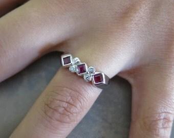 14K white gold ruby princess cuts and round diamonds.